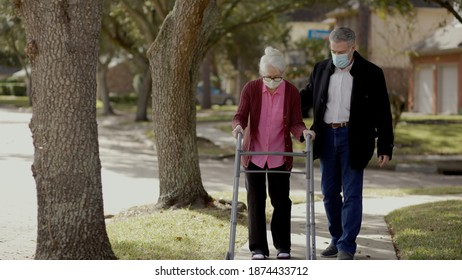 An elderly woman in mask due to the pandemic uses a walker to take a walk outdoors with a friend.