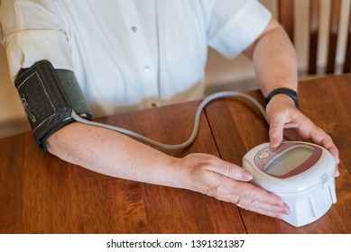 An elderly woman measures blood pressure with an electrical device. A pensioner uses a tonometer. Hands of an old woman