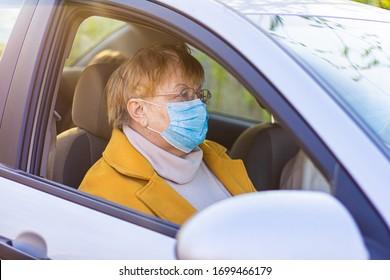 Eine ältere Frau in einer medizinischen Gesichtsmaske auf dem Beifahrersitz im Auto. Fahrt ins Krankenhaus während der Coronavirus Pandemie Konzept. Konzept für Fahrten, Reisen und alte Menschen - glückliches Seniorenpaar