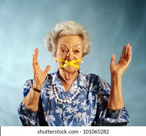 elderly woman with mouth taped closed