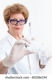 Elderly woman a nurse looks at syringe for vaccination in her hand, focus on the needle, white background