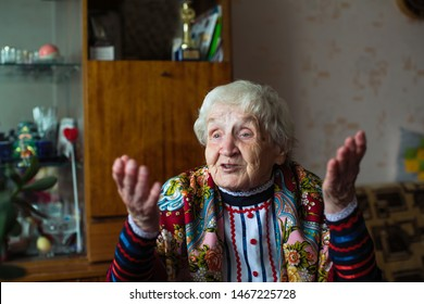 Elderly woman - old grandmother in bright clothes and a scarf gestures sitting at the table.