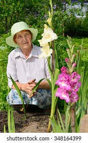 An elderly woman on a bed with white and purple gladioli.