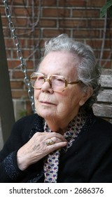 elderly woman on bench swing adjusting scarf