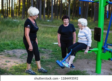 Elderly woman on a sports simulator, two women help her to do exercises.