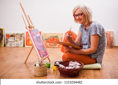 Elderly woman is painting in her home. Retirement hobby.
