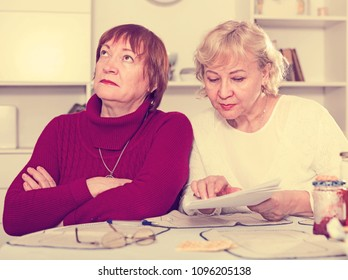 Elderly woman with papers in hand calming resentful female at home
