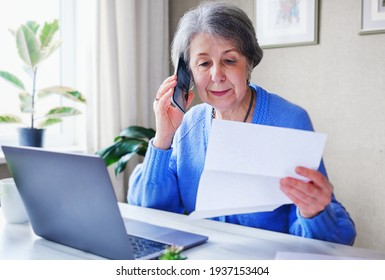 An elderly woman pays taxes or other bills online - A pensioner calls on the phone and finds out information about a loan or her savings - Online help concept for the elderly