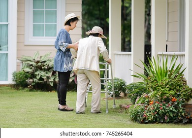 Elderly woman in physical therapy walking in backyard with daughter.