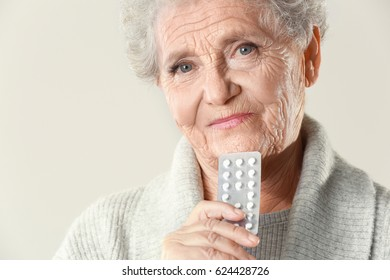 Elderly woman with pills on light background