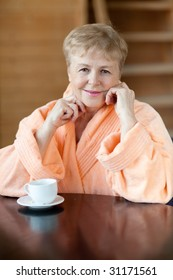 The elderly woman in a pink dressing gown looks in a camera