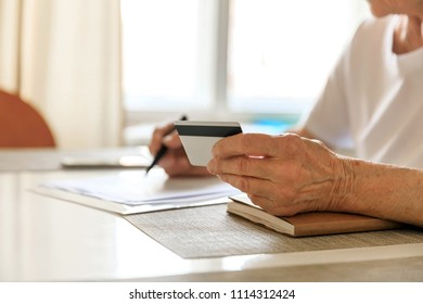 Elderly woman plans her budget, with a notebook, bills and a credit card. Increase in retirement age, savings for a retirement