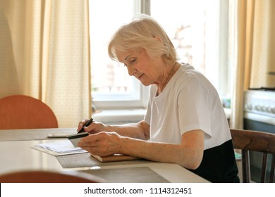 Elderly woman plans her budget, with a notebook, bills and a credit card, payment online. Increase in retirement age, savings for a retirement