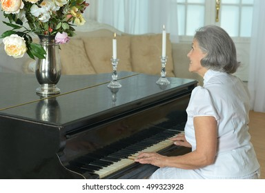 Elderly woman playing the piano at home