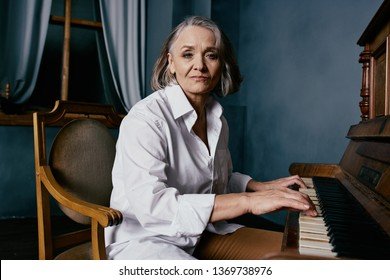 Elderly woman playing the piano indoors