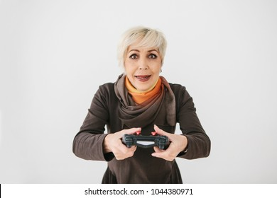 An elderly woman plays a video game and gestures that she won. Elderly person and modern technology.