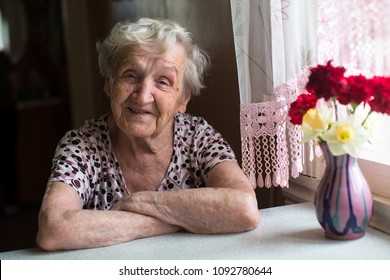 Elderly woman portrait near window in the house.