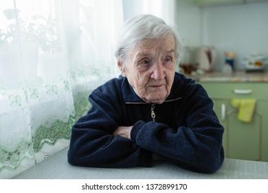 Elderly woman portrait near window in the house.