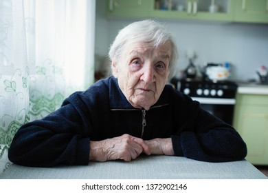 An elderly woman portrait near window in the house.