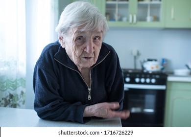 An elderly woman portrait near window in the house.
