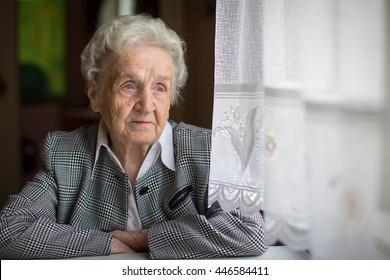 Elderly woman portrait, sitting in the house.