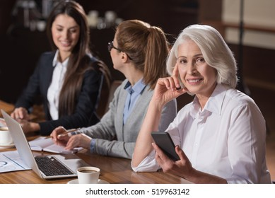 Elderly woman posing with her young colleagues