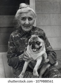 Elderly woman posing with pug dog