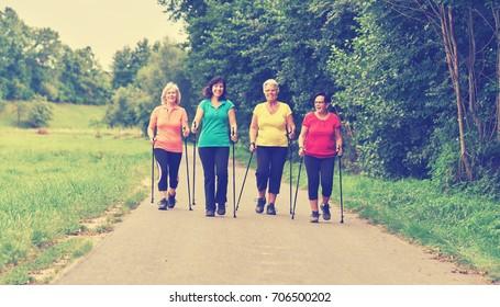 elderly woman practicing nordic walking in nature