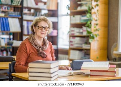 An elderly woman preparing for the exam in the library
