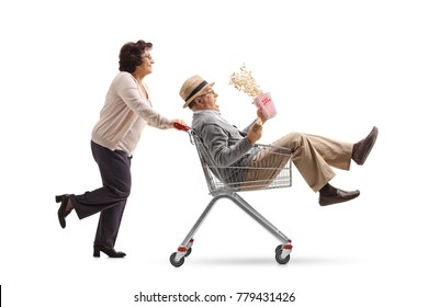 Elderly woman pushing a shopping cart with a mature man with a popcorn box riding inside isolated on white background