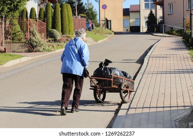 An elderly woman is pushing a wheelbarrow with a package of garbage in front of her. Removal of household waste. Ordinary life on the street neblshogo city. Recycling and recycling products.