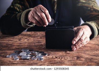 Elderly woman putting coin to wallet.