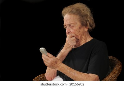 Elderly woman puzzled by an electronic device