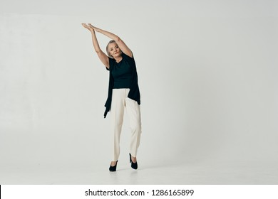 an elderly woman raised her arms up and leaned to the side on a light background in full growth
