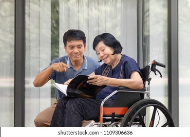 Elderly woman reading a book on wheelchair with her son take care.
