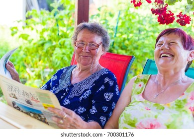 Elderly woman reading joke for her sitting and laughing retired friend in park.
