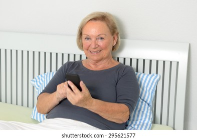 Elderly woman reading an sms on her mobile phone with a smile of pleasure as she relaxes on her bed sitting up against the cushions