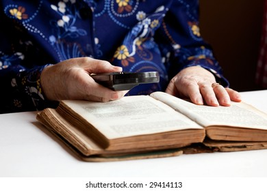 An elderly woman reading a very old book