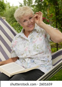 The elderly woman reads the book in a garden