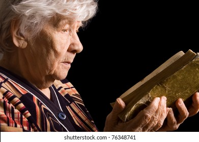 Elderly woman reads the book on black