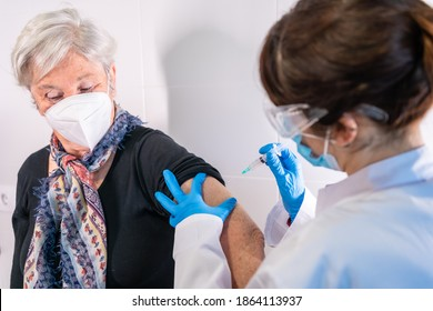 An elderly woman receiving the injection of the coronavirus vaccine by a doctor to receive the antibodies, immunize the population. side effects, risk people, antibodies, new normal, covid-19. - Shutterstock ID 1864113937