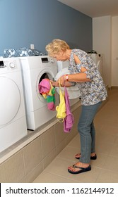 Elderly woman removing dried clothing from a drier machine in a laundry room