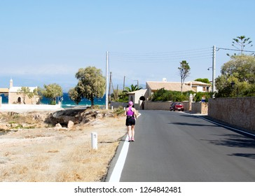 An elderly woman runs along the road against the backdrop of the sea coast on an island in Greece. Sports in the summer outside, jogging middle-aged women view from the back