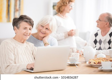Elderly woman searching for news on the internet using a laptop during meeting with friends