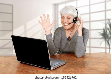 elderly woman senior at the computer communicates laptop, grandmother