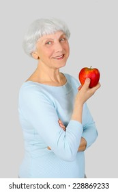 elderly woman senior with red yellow apple in hands on a light background in the studio,  grandmother