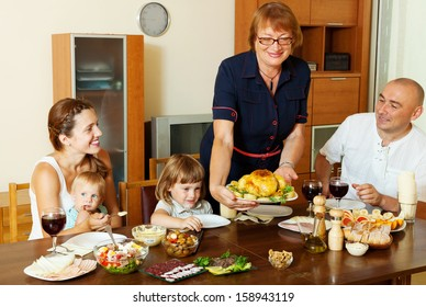elderly woman serving baked chicken to table for her family