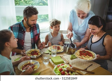 Elderly woman serving meal to her family at home