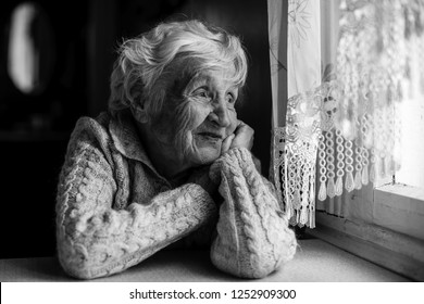 An elderly woman sits and looks out the window.