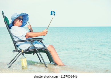 An elderly woman sits on the beach on a chaise longue, drinking wine and making photo against the background of the sea.
